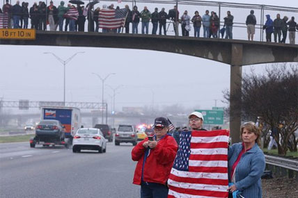 Supporters of Chris Kyle in Midlothian,Texas, line up along the southbound lane of Interstate 35, Tuesday, Feb. 12, 2013, in Waco, Texas, for his final journey to Austin, where he will be buried.