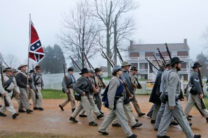 Confederate troops march in front of the McLean House during a re-enactment of the Battle of Appomattox Courthouse as part of commemoration of the surrender of the Army of Northern Virginia Thursday, April 9, 2015. (AP Photo/Steve Helber)