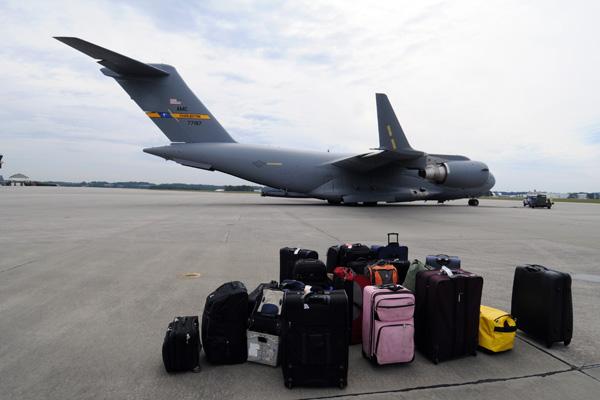 Luggage on an airstrip next to a cargo plane.