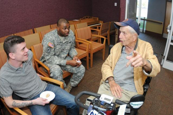 Older veteran in a wheelchair talking with service members.