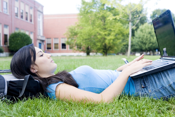 College student using a laptop outdoors.