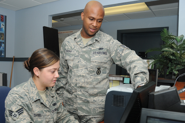 Airmen at a computer, teaching and education.