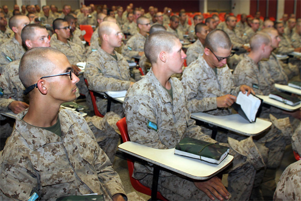 Marines in class at their desks listening to a lecture.