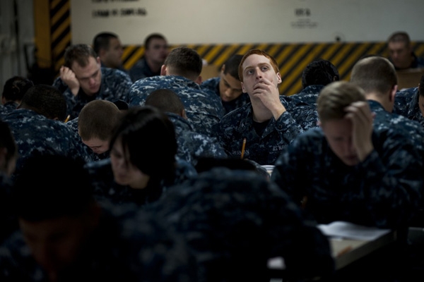 Navy sailors taking tests at desks.