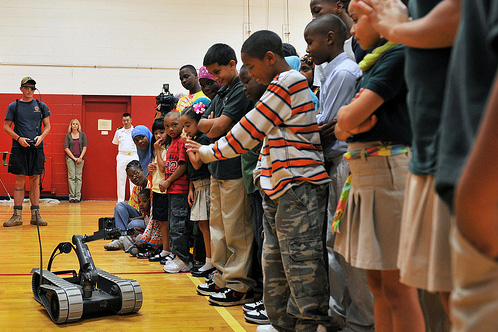 School children standing in line at a gym watching a packbot.