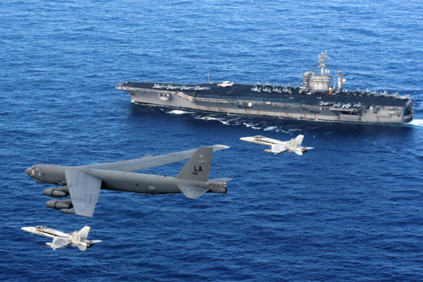An Air Force B-52 Stratofortress flies past the Navy aircraft carrier USS Nimitz escorted by two Navy F  A-18 Hornets. A B-52 recently flew over contested territory in the South China Sea