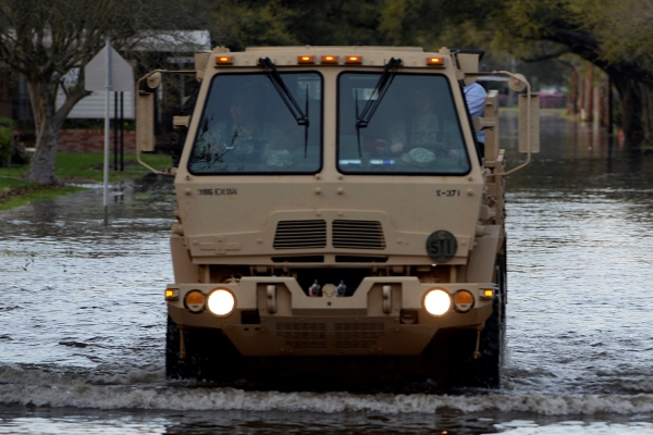 A Texas Army National Guard Light Medium Tactical Vehicle drives through flooded streets in Orange, Texas, March 17, 2016. (Photo by Alicia Lacy/Air National Guard)