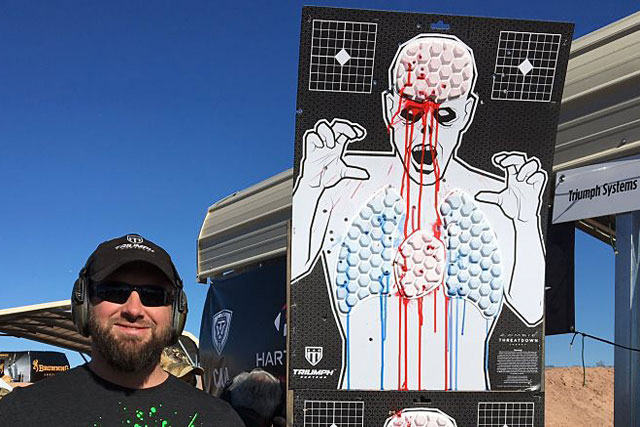"Jared Ogden, a former NAVY SEAL who recently launched his own business, Triumph Systems, stands near Threat Down, a zombie or humanoid target with vital areas that ""bleed"" when shot, on Jan. 16, 2017, at SHot Show. Military.com photo"