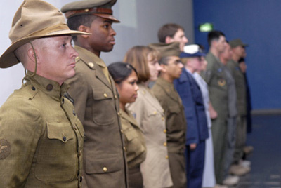 Airmen showing off historical uniforms in a lineup.