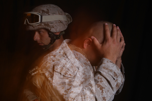 Stressed soldier with head in hands.