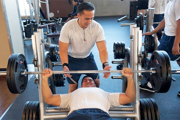 Victor Dioguino assists Matthew McLaughlin while lifting weights at the Warrior Fitness Center June 17, 2013, at Nellis Air Force Base, Nev. (U.S. Air Force/Caitlin Kenney)