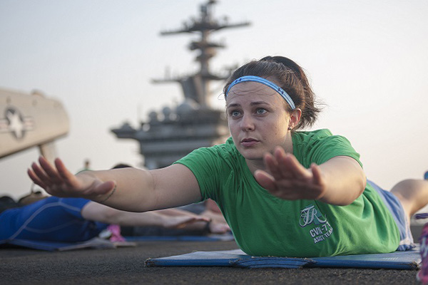 Navy Master-At-Arms 2nd Class Nichole Lowery instructs Sailors during sunrise yoga