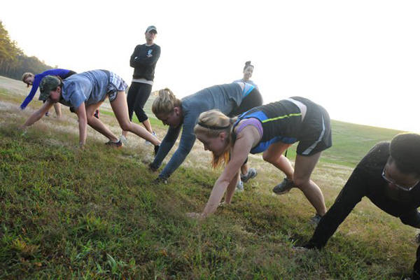 Fort Rucker 'Boot Camp' participants bear crawl up a hill during one of their early morning workouts.