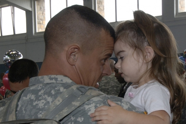 A servicemember hugging his daughter