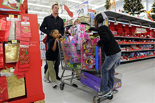 "Atlanta Falcons quarterback Matt Ryan helps children push a cart of toys while he and teammates participated in the ""Shop with a Jock"" program, which provides a $100 gift card and a shopping experience to children from an Atlanta-area mission."