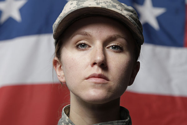 female soldier with American flag in the background