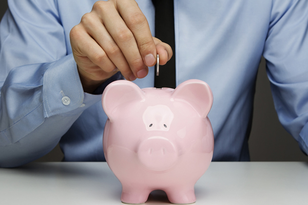Businessman drops coin in pink piggy bank.
