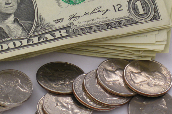A stack of dollar bills and quarters.