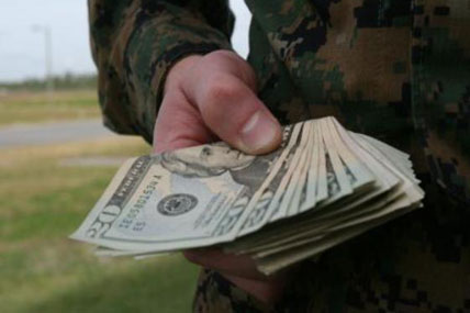 Soldier holds a stack of cash.