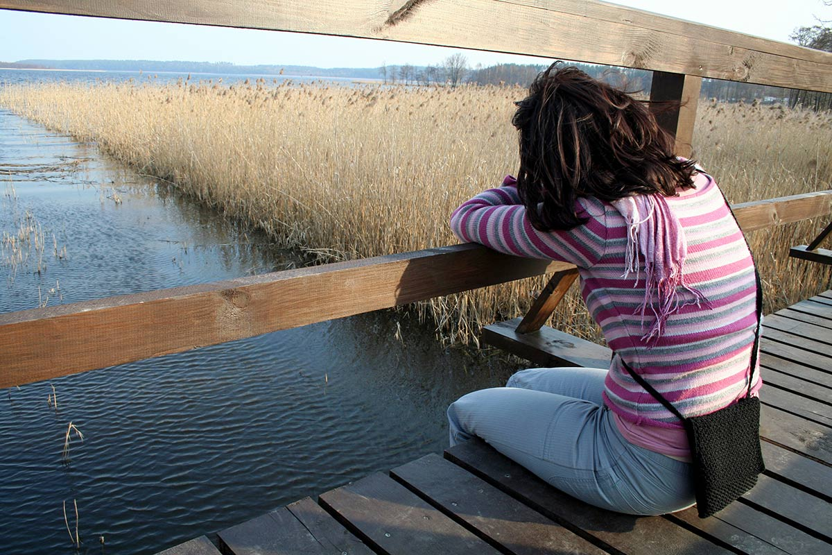 A sad woman sitting on a bridge over a marsh