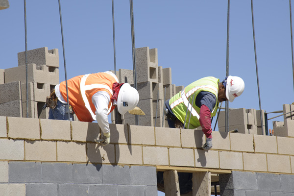 Two construction workers laying cinder blocks.