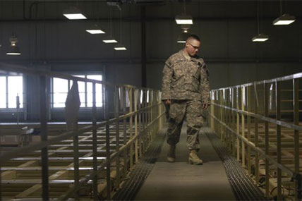 A U.S. military guard watches over detainee cells inside the Parwan detention facility near Bagram Air Field in Afghanistan. Saturday, March 23, 2013
