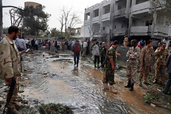 Security personnel inspect the site of a car bomb that targeted the French embassy in Libya on Tuesday. Two French guards were wounded in the attack. An explosives-laden car was detonated just outside the embassy. AP photo