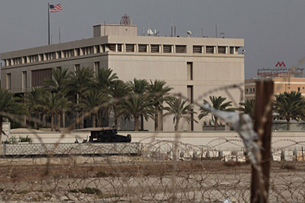 A Bahraini armored personnel vehicle and personnel reinforce U.S. Embassy security just outside of a gate to the building, surrounded in barbed wire, in Manama, Bahrain, on Sunday, Aug. 4, 2013.