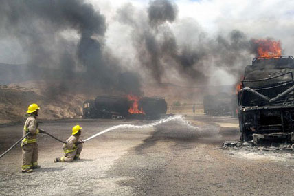 Firefighters try to put out burning NATO supply trucks in Samangan, north of Kabul, Afghanistan, on Wednesday. Afghan officials say a magnetic bomb placed on a truck exploded and destroyed 22 NATO supply vehicles in northern Afghanistan.