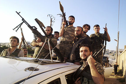 In this citizen journalism image provided by Shaam News Network SNN, taken on Sunday, Aug. 12, 2012, Free Syrian Army soldiers pose for a photograph, in Sarmada, Idlib province, northern Syria.