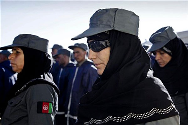 Afghan policewomen and policemen stand at attention during their graduation ceremony in Herat west of Kabul, Afghanistan, Thursday, Dec. 20, 2012.