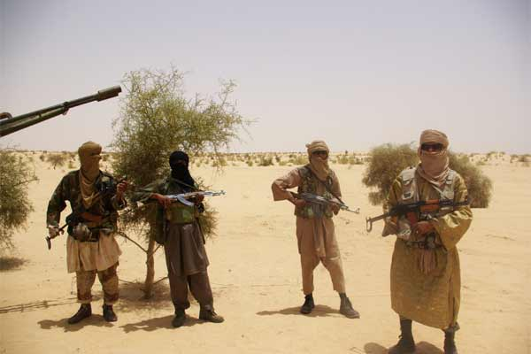 Fighters from Islamist group Ansar Dine stand guard during a hostage handover in the desert outside Timbuktu, Mali