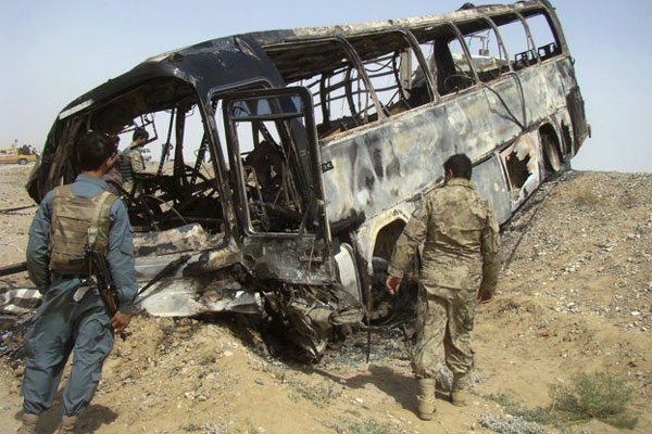 Afghan police and army soldiers inspect a burned bus after it collided with the wreckage of a truck that was attacked by Taliban insurgents in Maiwand district, on the highway between Kandahar and Helmand, Afghanistan, Friday, April 26, 2013.
