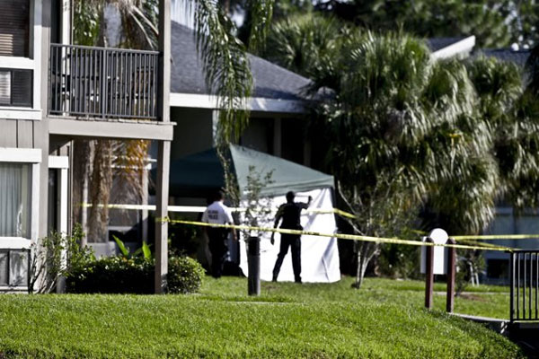 Investigators stand outside an apartment complex where a man was fatally shot when a team of FBI agents swarmed his home early Wednesday, May 22, 2013, in Orlando, Fla. (AP Photo/John Raoux)