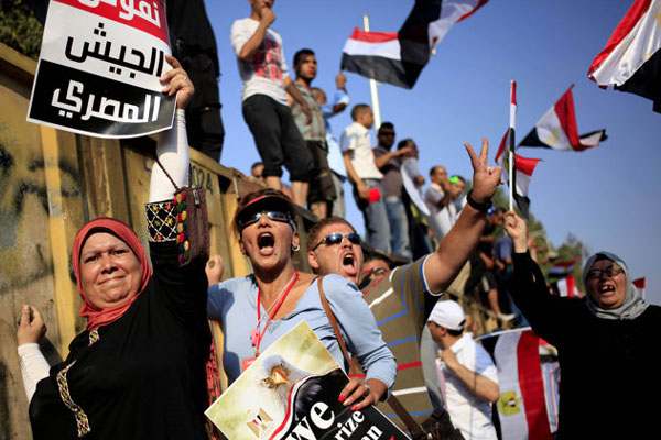 Opponents of Egypt's Islamist President Mohammed Morsi chant slogans during a protest outside the presidential palace, in Cairo, Egypt, Wednesday, July 3, 2013. (AP Photo/Khalil Hamra)