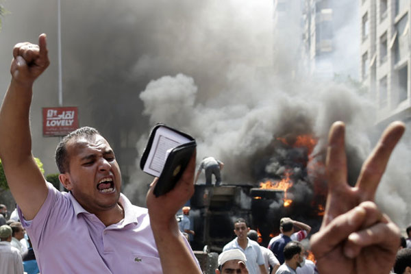 Supporters of Egypt's ousted President Morsi chant slogans against Egyptian Defense Minister Gen. Abdel-Fattah el-Sissi during clashes with Egyptian security forces in Cairo's Mohandessin neighborhood, Egypt,, Aug. 14, 2013. (AP Photo/Hassan Ammar