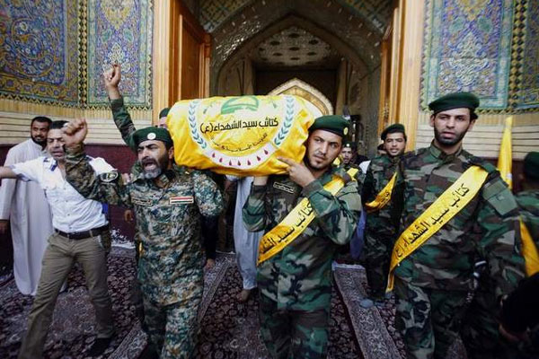Members of a Shiite militant group chant slogans against the Sunni-dominated Free Syrian Army rebel group and the al-Qaida-affiliated Jabhat al-Nusra, as they carry the coffin of a Shiite fighter during a funeral procession.