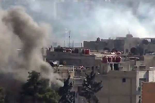 In this image taken from video obtained from the Shaam News Network, which has been authenticated based on its contents and other AP reporting, smoke rises from buildings due to heavy clashes between Free Syrian army fighters and government forces.