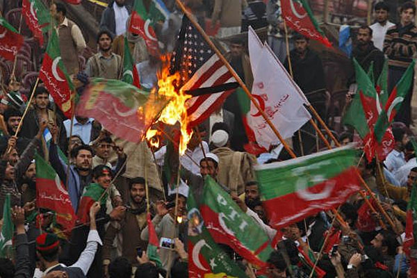 Supporters of Pakistan's Tehreek-e-Insaf party, headed by cricketer-turned politician Imran Khan, wave their party's flag while burning a representation of a U.S. flag during a protest against U.S. drone strikes in Pakistan, in Peshawar, Pakistan.