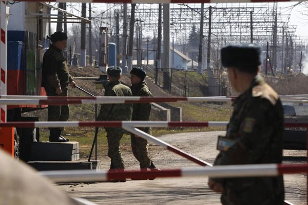 In this photo taken Monday, March 24, 2014, a Ukrainian border guard, right, and Russian border guards, background, stand at the crossing between Ukraine and Russia in the village of Vyselki, eastern Ukraine. (AP Photo/Sergei Grits)