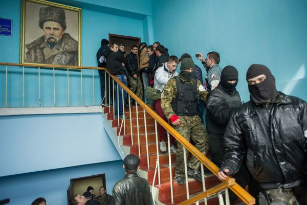 Crimean pro-Russian self-defense forces walk through the Ukrainian navy headquarters, with a picture of 19th century Ukrainian poet and writer Taras Shevchenko, in Sevastopol, Crimea, Wednesday, March 19, 2014. Photo: Andrew Lubimov, AP