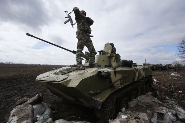 A Ukrainian soldier stands atop an armored vehicle at a military camp near the village of Michurino, Ukraine, on, March 17, 2014. (AP Photo/Sergei Grits)