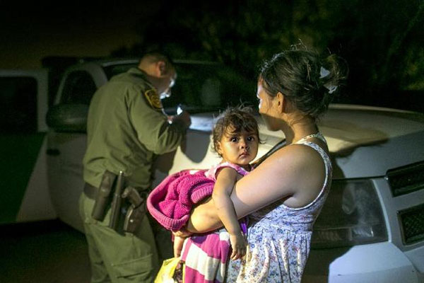 Flor Garcia, 19, of Honduras, holding her one-year-old daughter, Flor Fernandez, turned themselves over to Customs and Border Protection Services agents after crossing the Rio Grande. (AP Photo/Austin American-Statesman, Rodolfo Gonzalez)