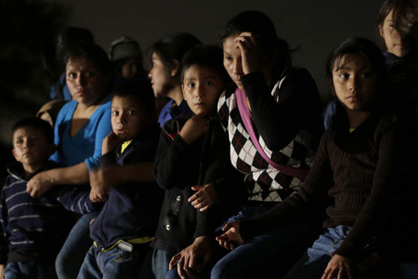 FILE - In this June 25, 2014 photo shows a group of immigrants from Honduras and El Salvador who crossed the U.S.-Mexico border illegally are stopped in Granjeno, Texas. (AP Photo/Eric Gay, File)