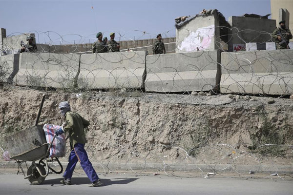 An Afghan laborer walks past a gate of Camp Qargha as Afghanistan National Army soldiers stand guard, west of Kabul, Afghanistan, Tuesday, Aug. 5, 2014. (AP Photo/Massoud Hossaini)