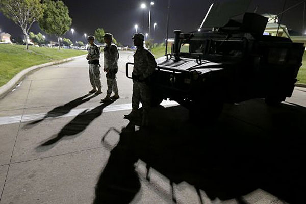 Members of the Missouri National Guard stand watch outside a command post near a protest Monday, Aug. 18, 2014, for Michael Brown, who was killed by a police officer Aug. 9 in Ferguson, Mo. (AP Photo/Charlie Riedel)