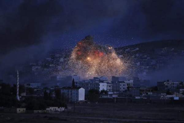 Smoke and flames from an airstrike by the U.S.-led coalition rise in Kobani, Syria, as seen from a hilltop on the outskirts of Suruc, at the Turkey-Syria border, on Monday. (AP photo)