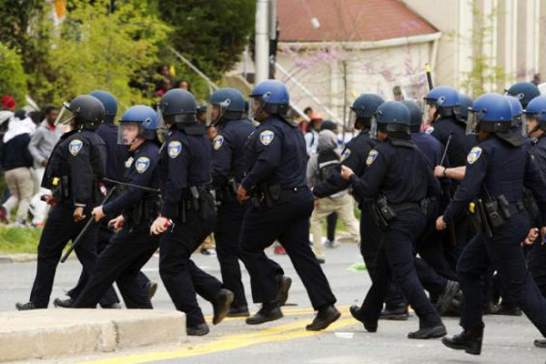 Baltimore police officers push back demonstrators who are throwing rocks at the police, after the funeral of Freddie Gray, Monday, April 27, 2015, at New Shiloh Baptist Church in Baltimore. (AP Photo/Jose Luis Magana)
