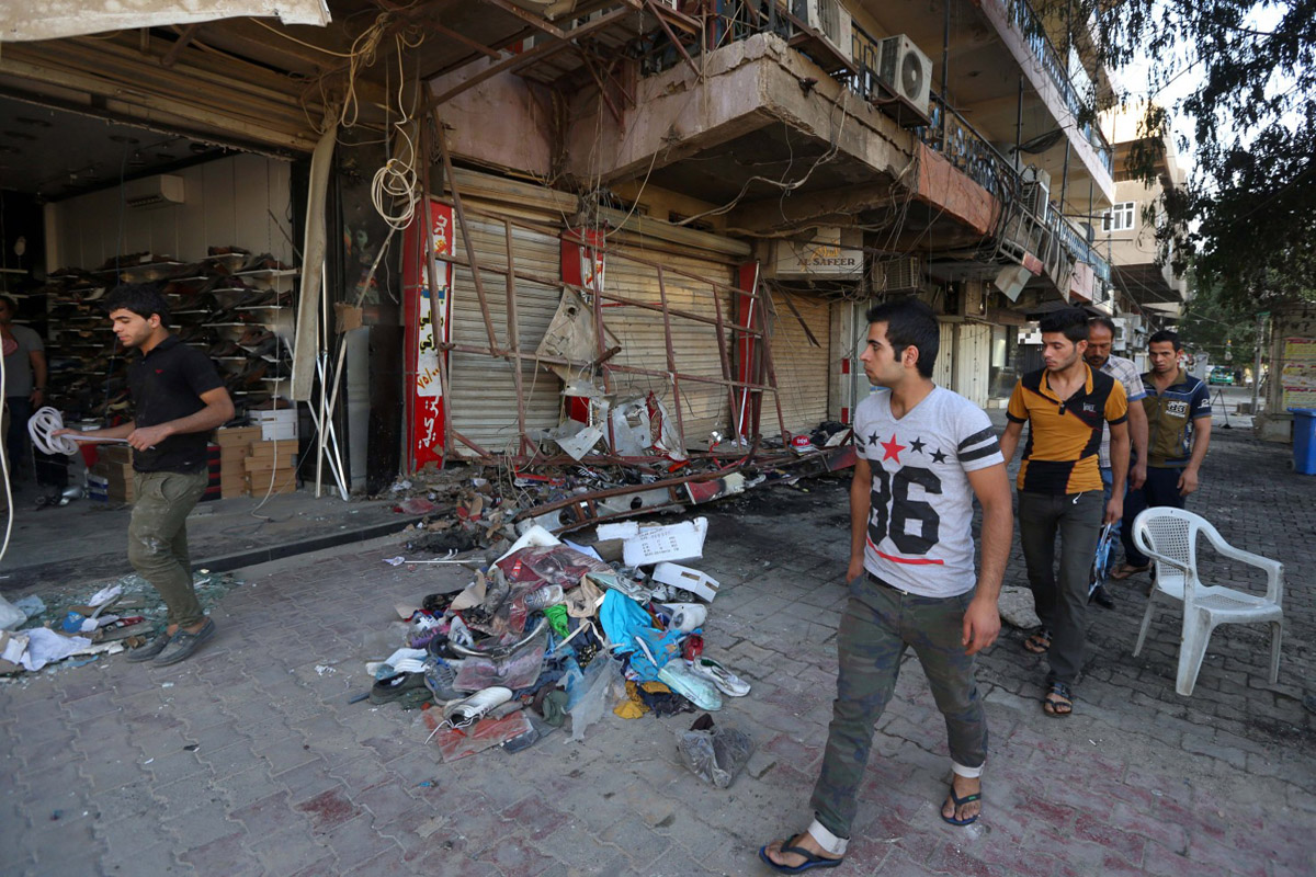 Civilians inspect the site of a bomb attack near restaurants and coffee shops filled with customers in central Baghdad on Sunday, May 3, 2015. Police say two bombs killed more than a dozen civilians. (Hadi Mizban/Associated Press)