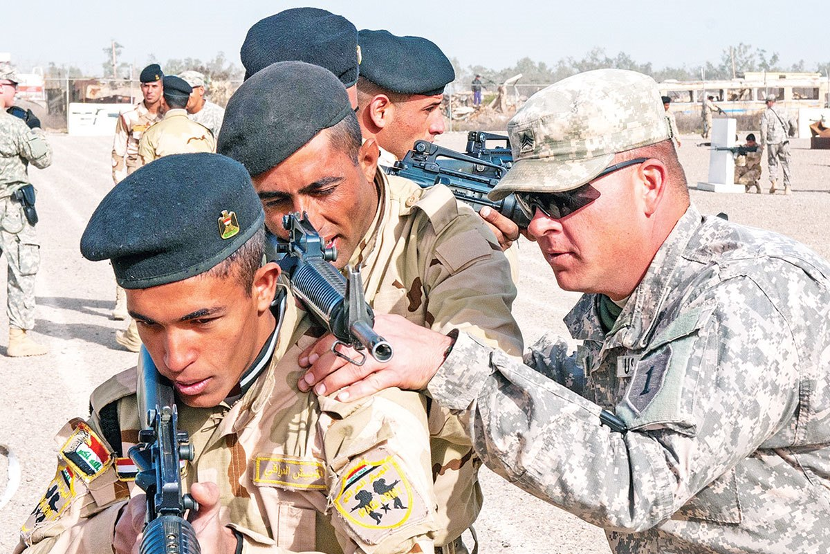 Sgt. David Kappel (right), an infantry trainer assigned to 1st Armored Brigade Combat Team, 1st Infantry Division, adjusts the rifle of an Iraqi army trainee Jan. 7 a
